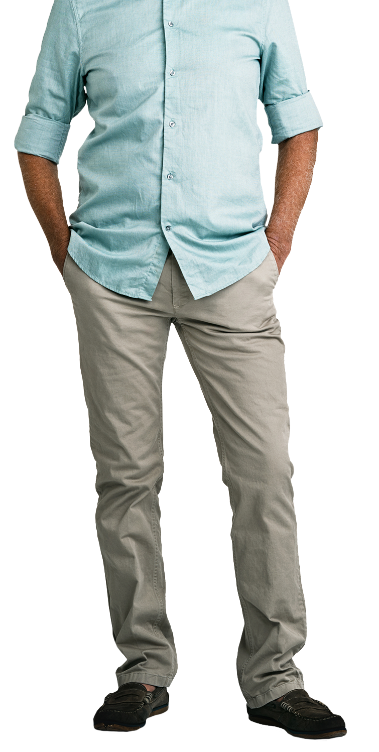 Smiling man standing with his hands in his pockets.